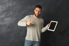 Homme bel tenant le comprimé numérique et se dirigeant là-dessus Photographie stock