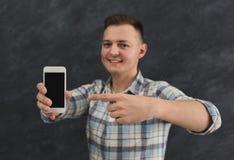 Homme bel tenant le smartphone dans le studio Images stock