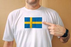 Homme bel utilisant fièrement le T-shirt blanc avec le drapeau suédois Image stock