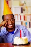Homme bel utilisant la chemise bleue et le chapeau se reposant par la table avec le gâteau dans le burning avant et simple de bou Images libres de droits