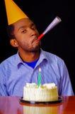 Homme bel utilisant la chemise bleue et le chapeau se reposant par la table avec le gâteau dans le burning avant et simple de bou Images stock
