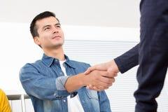 Homme bel utilisant la chemise occasionnelle de treillis faisant la poignée de main dans l'o image stock