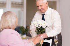 Homme bel vaillant donnant des fleurs Photographie stock