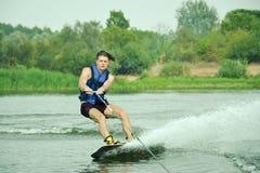 Homme bel wakesurfing dans un lac photographie stock