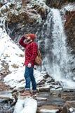 Homme berded bel marchant près de la cascade aux montagnes en hiver Photographie stock libre de droits