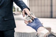 Homme bienfaisant dans le costume foncé d'affaires donnant l'argent photographie stock