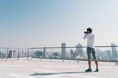 Homme blanc prenant la photo de paysage urbain sur le dessus de toit de bâtiment le jour ensoleillé Passe-temps de photographie,  Image stock