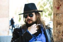 Homme blanc sexy avec des lunettes de soleil et un chapeau de chapeau feutré fumant une cigarette Photo stock