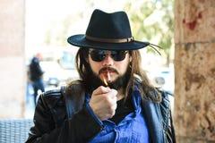 Homme blanc sexy avec des lunettes de soleil et un chapeau de chapeau feutré fumant une cigarette Images stock