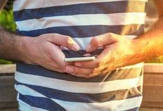 Homme blanc tenant le téléphone intelligent en parc de ville dehors avec le soleil brûlant photographie stock libre de droits