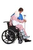 Homme blessé dans le fauteuil roulant avec l'infirmière photo libre de droits