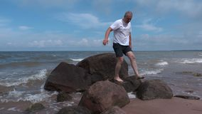 Homme blessé sur les pierres par la mer banque de vidéos