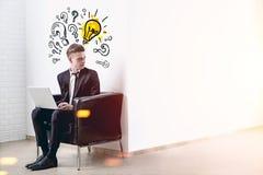 Homme blond avec un ordinateur portable, des questions et l'idée Photographie stock libre de droits