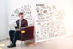 Homme blond avec un ordinateur portable, plan d'affaires Images stock