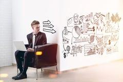 Homme blond avec un ordinateur portable, plan d'affaires, flèches Image libre de droits