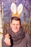 Homme blond drôle en parc avec des oreilles de lapin image stock