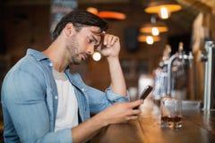 Homme bouleversé employant le mobile au bar Images stock