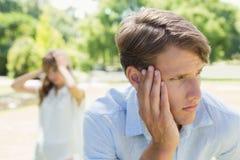 Homme bouleversé pensant après un combat avec son amie en parc Photos stock