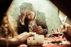 Homme bouleversé regardant des cartes de tisonnier à disposition Image libre de droits