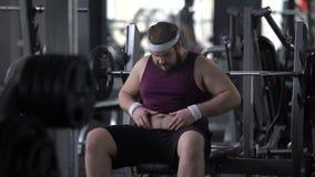 Homme bouleversé regardant son gros estomac, désir de perdre le poids, séance d'entraînement de gymnase, sport clips vidéos