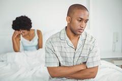 Homme bouleversé s'asseyant sur le lit après argument Image stock