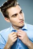 Homme boutonnant la chemise Photos libres de droits