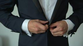 Homme boutonnant un bouton sur sa veste banque de vidéos