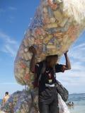 Homme brésilien rassemblant la plage Rio d'Ipanema de boîtes Photographie stock libre de droits