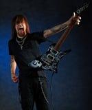 Homme brutal avec la guitare électrique Photographie stock libre de droits