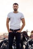 Homme brutal près de sa motocyclette de coutume de coureur de café photos stock