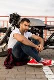 Homme brutal près de sa motocyclette de coutume de coureur de café Photographie stock