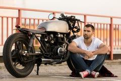Homme brutal près de sa motocyclette de coutume de coureur de café Photo stock