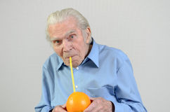 Homme aîné buvant du jus d'orange frais Photo stock