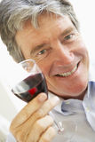 Homme buvant une glace de vin rouge Photo stock