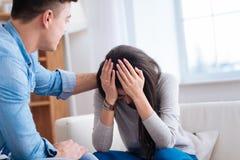 Homme calmant la femme déprimée vers le bas contrariée Image stock