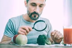 Homme calme indifférent étudiant différents types de légumes photos stock