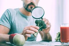 Homme calme sérieux étudiant différents genres de légumes photographie stock