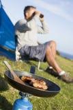 Homme campant à l'extérieur et faisant cuire Images libres de droits