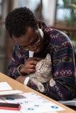 Homme caressant son chat préféré tout en travaillant images stock