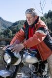 Homme caressant une motocyclette Image stock