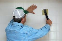 Homme cassant vers le haut un mur de salle de bains Photo libre de droits