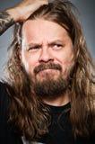Homme caucasien avec de longs cheveux semblant confus Photographie stock