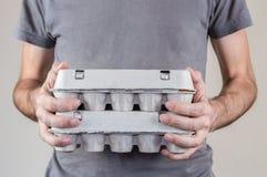Homme caucasien avec le T-shirt gris jugeant deux boîtes à oeufs de carton pleines des oeufs de poulet sur un fond blanc photos stock