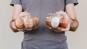Homme caucasien avec le T-shirt gris jugeant deux boîtes à oeufs en plastique pleines des oeufs de poulet images stock