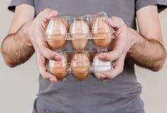 Homme caucasien avec le T-shirt gris jugeant deux boîtes à oeufs en plastique pleines des oeufs de poulet image libre de droits