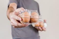 Homme caucasien avec le T-shirt gris montrant une boîte à oeufs en plastique complètement d'oeufs de poulet photos libres de droits