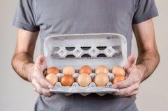 Homme caucasien avec le T-shirt gris tenant une boîte à oeufs de carton complètement d'oeufs de poulet sur un fond blanc images libres de droits