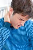 Homme caucasien ayant un neckache dans la salle de séjour Images stock