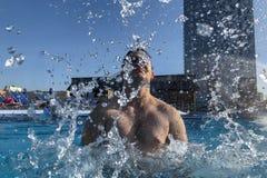 Homme caucasien bel éclaboussant dans la piscine photographie stock