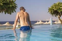 Homme caucasien bel sexy s'asseyant dans la piscine extérieure dessus photos stock